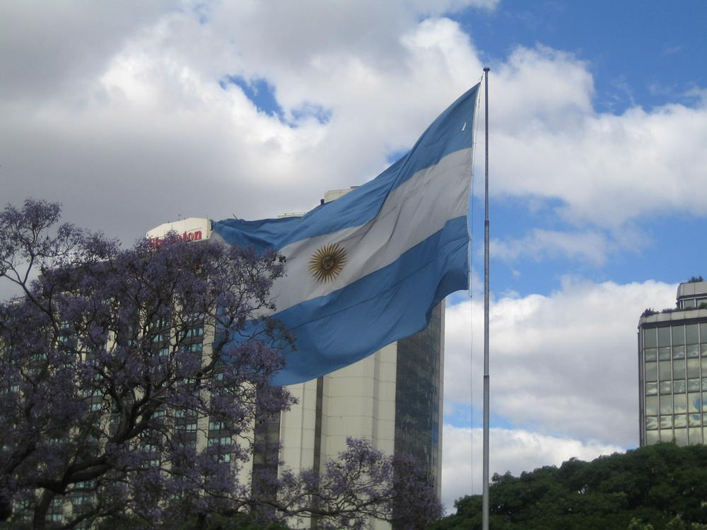 Argentine flag flying with skyscrapers in background