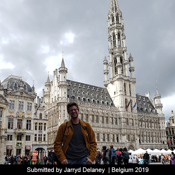 A student stands in front of the palace in Belgium.
