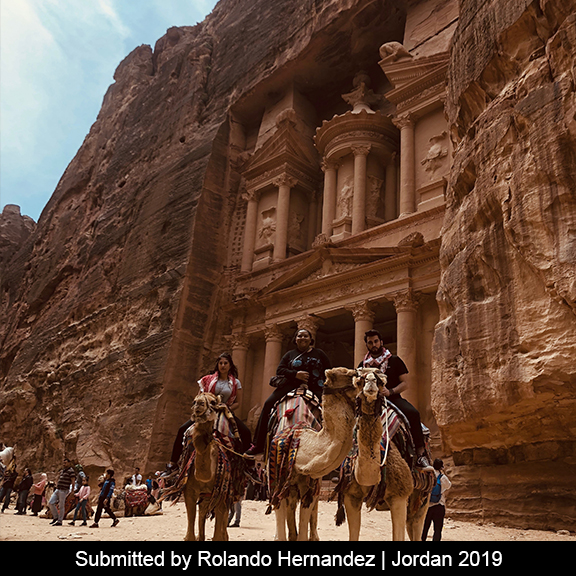 Three students sit on camels in front of Petra.